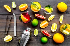 Mix exotic fruit cocktail with alcohol. Shaker and strainer near citrus fruits and glass with cocktail on dark wooden. Background top view stock photos