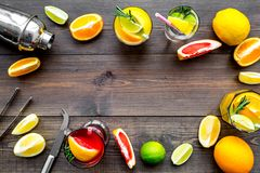 Mix exotic fruit cocktail with alcohol. Shaker and strainer near citrus fruits and glass with cocktail on dark wooden. Background top view royalty free stock photography