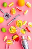 Mix exotic fruit cocktail with alcohol. Shaker and strainer near citrus fruits and glass with cocktail on pink. Background top view royalty free stock photo
