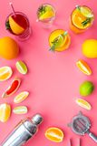 Mix exotic fruit cocktail with alcohol. Shaker and strainer near citrus fruits and glass with cocktail on pink. Background top view stock photo