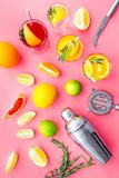 Mix exotic fruit cocktail with alcohol. Shaker and strainer near citrus fruits and glass with cocktail on pink. Background top view royalty free stock image