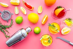 Mix exotic fruit cocktail with alcohol. Shaker and strainer near citrus fruits and glass with cocktail on pink. Background top view stock photography
