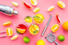Mix exotic fruit cocktail with alcohol. Shaker and strainer near citrus fruits and glass with cocktail on pink. Background top view royalty free stock images
