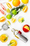Mix exotic fruit cocktail with alcohol. Shaker and strainer near citrus fruits and glass with cocktail on white. Background top view stock photography