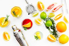 Mix exotic fruit cocktail with alcohol. Shaker and strainer near citrus fruits and glass with cocktail on white. Background top view royalty free stock images
