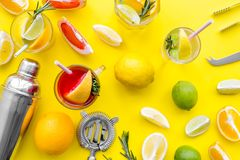 Mix exotic fruit cocktail with alcohol. Shaker and strainer near citrus fruits and glass with cocktail on yellow. Background top view royalty free stock image