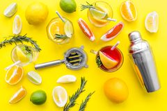 Mix exotic fruit cocktail with alcohol. Shaker and strainer near citrus fruits and glass with cocktail on yellow. Background top view stock photos