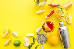 Mix exotic fruit cocktail with alcohol. Shaker and strainer near citrus fruits and glass with cocktail on yellow. Background top view royalty free stock photo
