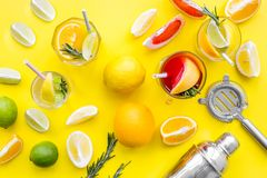 Mix exotic fruit cocktail with alcohol. Shaker and strainer near citrus fruits and glass with cocktail on yellow. Background top view stock photography