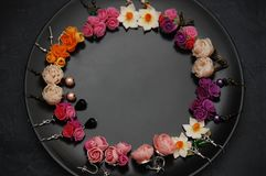 Mix of Fake Colorful Plastic Mini Flowers Earings Black Round Plate Copy space. Craft, Art, Hobby concept. Stock Image