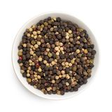 Mix of four types peppercorns in bowl isolated on white background. Top view.  royalty free stock photos