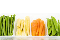 Mix of fresh baby vegetables. Fresh baby vegetables - carrots, beans, corn, in a casserole. Isolated over white Royalty Free Stock Image