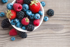 Mix of fresh berries in a basket on rustic wooden background. Close up, top view, high resolution product. Harvest Concept Royalty Free Stock Photography