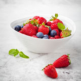 Mix fresh berries, blueberry strawberry, raspberry. Fresh berries, blueberry, strawberry, raspberry with mint leaves in a white ceramic bowl on a gray stone Royalty Free Stock Photos