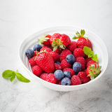 Mix fresh berries blueberry, strawberry, raspberry. Fresh berries, blueberry, strawberry, raspberry with mint leaves in a white ceramic bowl on a gray stone Royalty Free Stock Image
