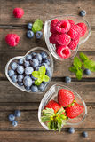Mix of fresh berries in a glass ramekins in shape of heart, on w Royalty Free Stock Photo