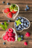 Mix of fresh berries in a glass ramekins in shape of heart, on w Stock Images