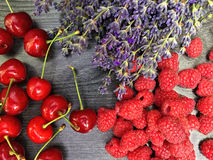 Mix of fresh berries and lavender flowers. On black wooden background summer organic berry, cherries and raspberry Stock Images