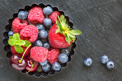 Mix of fresh berries in a small round metal backing mold, on sto Royalty Free Stock Photo