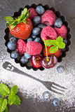 Mix of fresh berries in a small round metal backing mold and sug Stock Photo