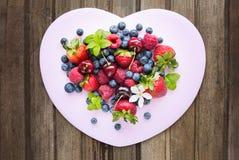 Mix of fresh berries in three  glass ramekins in shape of heart, Stock Photo