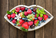 Mix of fresh berries on a white plate in shape of lips, on woode Stock Image