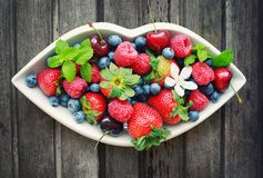 Mix of fresh berries in white plate in shape of lips, on wooden Stock Image