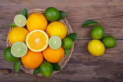 Mix of fresh citrus fruits in basket on  wood Stock Images