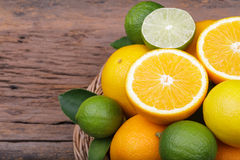 Mix of fresh citrus fruits in basket on  wood Royalty Free Stock Images
