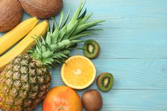 mix of fresh coconut, banana, kiwi fruit, orange and pineapple on blue wooden background. top view with copy space Royalty Free Stock Photography