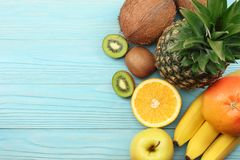 Mix of fresh coconut, banana, kiwi fruit, orange and pineapple on blue wooden background. top view with copy space royalty free stock images