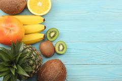 Mix of fresh coconut, banana, kiwi fruit, orange and pineapple on blue wooden background. top view with copy space stock images