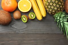 Mix of fresh coconut, banana, kiwi fruit, orange and pineapple on dark wooden background. top view with copy space stock image