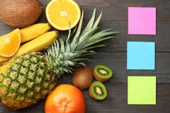 mix of fresh coconut, banana, kiwi fruit, orange and pineapple on dark wooden background. top view with copy space royalty free stock image