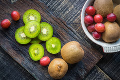 Mix of fresh fruits For good health . Kiwis , red grapes and Or. Ange on rustic wooden background . top view stock photos