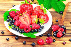 Mix of fresh, ripe berries in plate and spoon on wooden background. Royalty Free Stock Photos