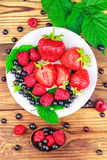Mix of fresh, ripe berries in plate and spoon on wooden background, top view. Royalty Free Stock Images