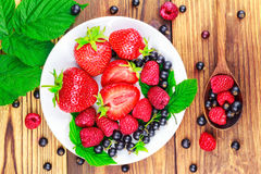 Mix of fresh, ripe berries in plate and spoon on wooden background, top view. Stock Photography