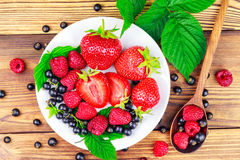 Mix of fresh, ripe berries in plate and spoon on wooden background, top view. Royalty Free Stock Image