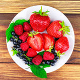 Mix of fresh, ripe berries in plate on wooden background. Stock Photos