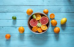 Mix of fresh ripe citrus fruits in a bowl on a blue background. High angle shot of sliced fresh juicy oranges, mandarines, lemons in a bowl and some whole stock photos