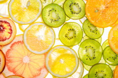 Mix of fresh transparent citrus fruits on white. Luminous background Royalty Free Stock Photography