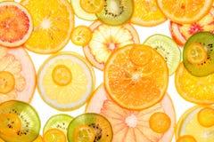 Mix of fresh transparent citrus fruits on white. Luminous background Stock Photos