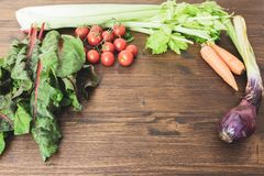 A mix of fresh vegetables on an old table ready to be cooked to Royalty Free Stock Photography