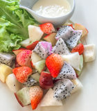 Mix fruit salad. Contains apple, strawberry, dragon fruit and rose apple with lettuce and salad dressing in white dish at restaurant. top view Royalty Free Stock Photography