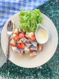 Mix fruit salad. Contains apple, strawberry, dragon fruit and rose apple with lettuce and salad dressing in white dish at restaurant. top view Stock Photo