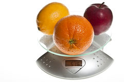Mix of fruits on food scale royalty free stock photography