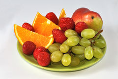 Mix of fruits on plate. Mix of strawberries, grapes, pear and orange slices on plate Royalty Free Stock Photos