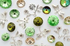 Green and gold crystals and metal bees and flowers and dragonflies on white background Royalty Free Stock Photo