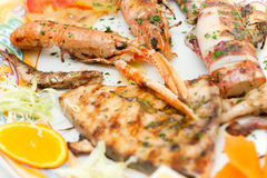 Mix grilled fish in a decorated dish. Royalty Free Stock Images